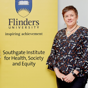 Portrait of Anne standing next to Fllinders University banner