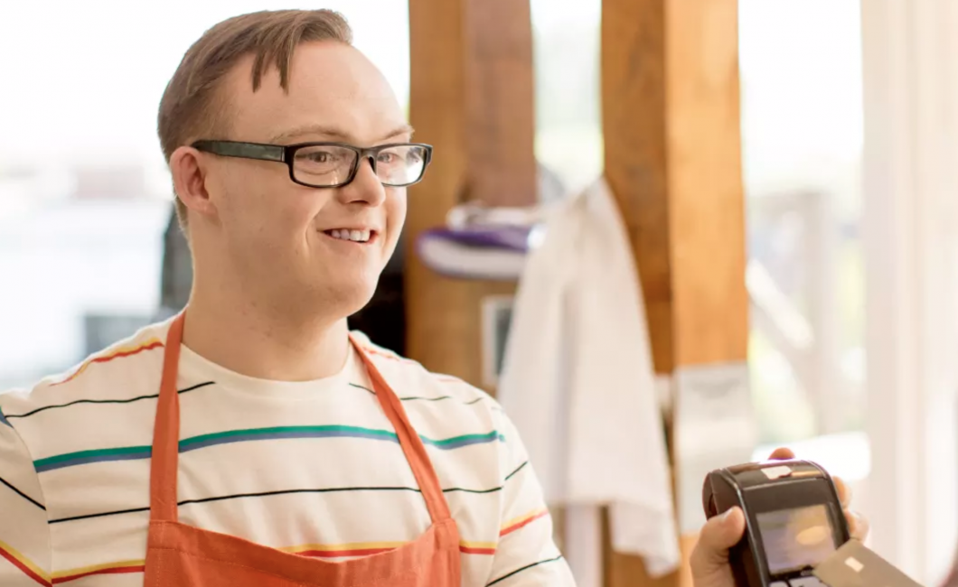 Young man with disability in an apron