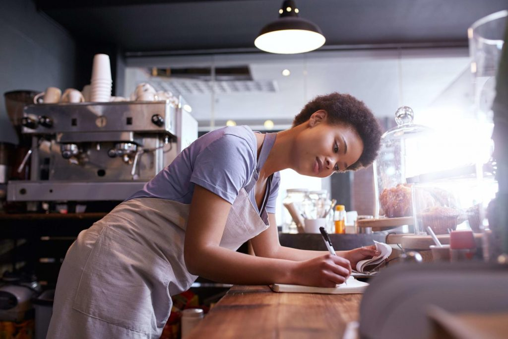 A young woman working at a cafe leaning on a counter doing some admin work