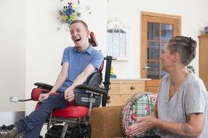 Color image of a real life young physically impaired ALS patient spending time with his mother at home. He is happy.
